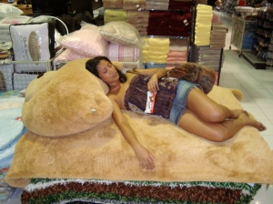 Asleep atop a pile of rugs in a Balinese home goods store, exhausted from Condom Zone preparation